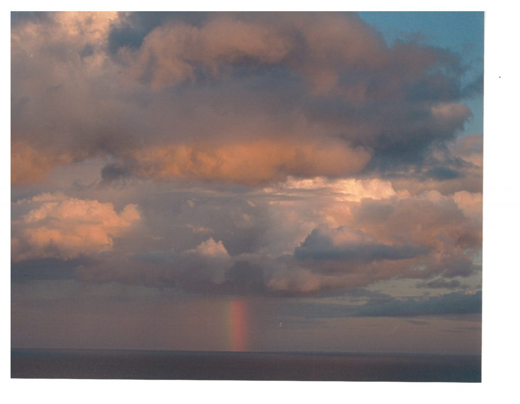 Grey and pink clouds over lake with rainbow